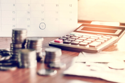 An image of a calculator, money and calendar on a desk