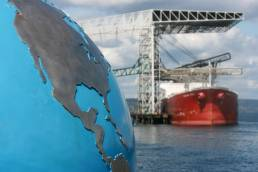 An image of a globe and a cargo ship in the distance